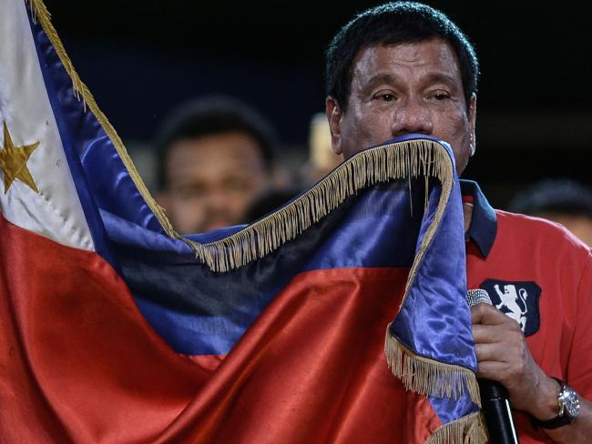Rodrigo Duterte kisses his national flag as he addresses his supporters during the Philippines election campaign.