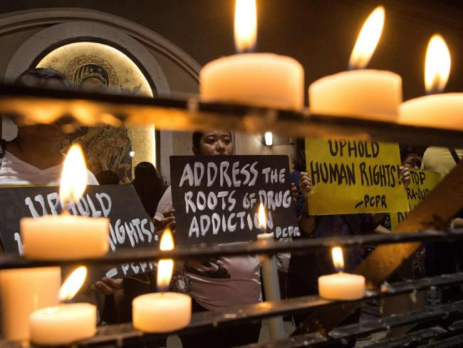 Human rights advocates hold placards condemning extrajudicial killings in the Philippines.