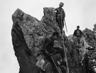 Three porters climbing along a ridge