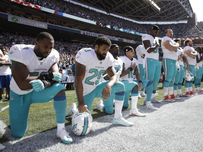 Miami Dolphins' (from left) Jelani Jenkins, Arian Foster, Michael Thomas, and Kenny Stills kneel during the singing of the national anthem before an NFL football game against the Seattle Seahawks on September 11, 2016, in Seattle. Picture: AP / Stephen Brashear
