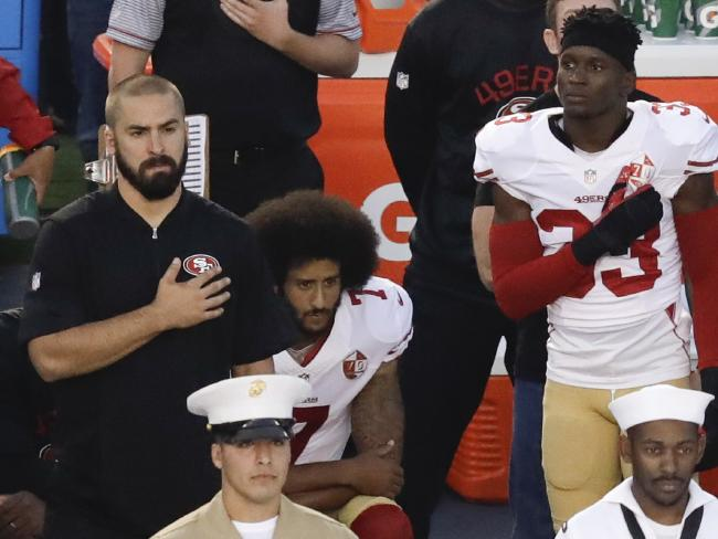 San Francisco 49ers quarterback Colin Kaepernick, middle, kneels during the national anthem before the team's NFL preseason football game against the San Diego Chargers, in San Diego. Picture: AP / Chris Carlson