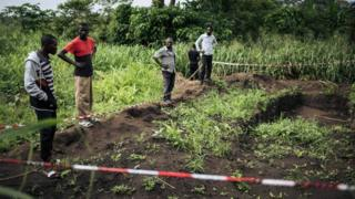 Survivors of an attack in the western village of Bongende, in the Democratic Republic of the Congo, stand on January 27, 2019, next to a mass grave that allegedly contains 100 bodies