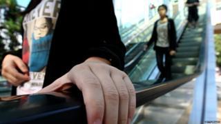person holds escalator handrail