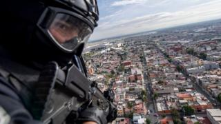 A policeman on board a helicopter as it flies over Mexico City in 2018