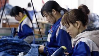Women sew jeans at a factory in China