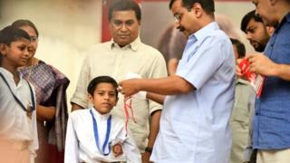 Delhi Chief Minister Arvind Kejriwal distributing masks to students