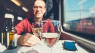 Man drinking wine on a train