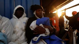 Rescued migrants rest on the migrant rescue ship Alan Kurdi