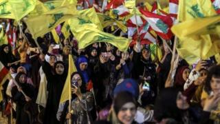 Hezbollah supporters wave Hezbollah flags as they listen to the speech of Hezbollah leader Hassan Nasrallah via a giant screen in southern suburb of Beirut, Lebanon, 14 August 2018