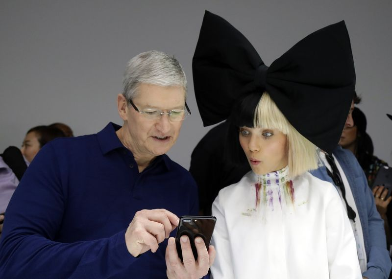Apple CEO Tim Cook shows an iPhone 7 to performer Maddie Ziegler during an event to announce new products Wednesday Sept. 7 2016 in San Francisco