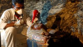 An Egyptian antiquities worker works on a coffin in the recently discovered tomb of Amenemhat, a goldsmith from the New Kingdom, at the Draa Abu-el Naga necropolis near the Nile city of Luxor
