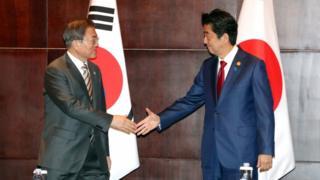 South Korean President Moon Jae-in shakes hands with Japanese Prime Minister Shinzo Abe in Chengdu, China, 24 December 2019