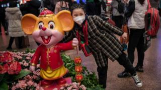 A young Chinese girl wears a protective mask as she stands next to a display celebrating the upcoming Year of the Rat