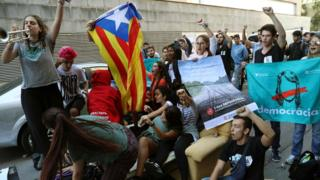 People stage a sit-down protest in front of the Unipost delivery companys offices in Terrassa