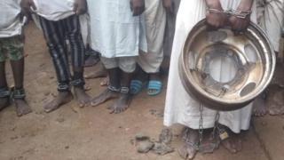 Captives are seen with chains around their ankles as police free them
