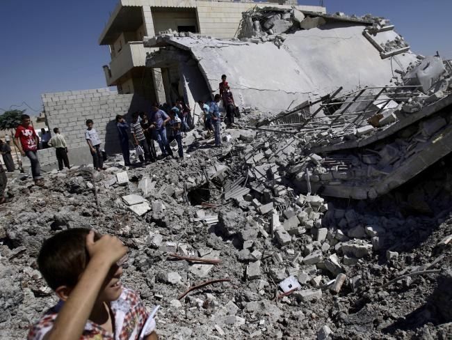 Syrians gather by the rubble of a house, destroyed from Syrian forces shelling, in the Syrian town of Azaz, on the outskirts of Aleppo, Syria. Picture: Muhammed Muheisen/AP
