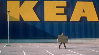 Man walking with a box infront of ikea sign