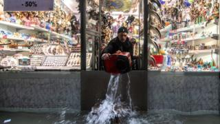 A shopkeeper uses a bucket to remove water from his property in Venice, 13 November 2019