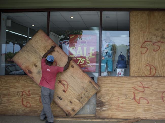 A worker removes plywood from shop windows after the passing of Hurricane Matthew in Kingston, Jamaica. Picture: AP