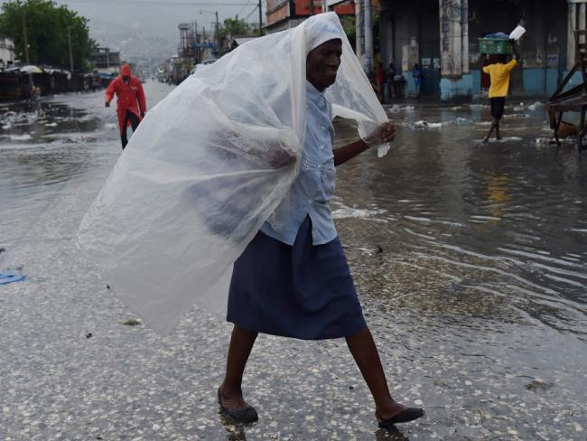 A woman protects herself from the rain with plastic after Hurricane Matthew, in Port-au-Prince. Picture: AFP
