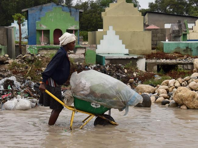 A woman pushes a wheelbarrow while walking in a partially flooded street, in the Haitian capital, Port-au-Prince. Picture: AFP