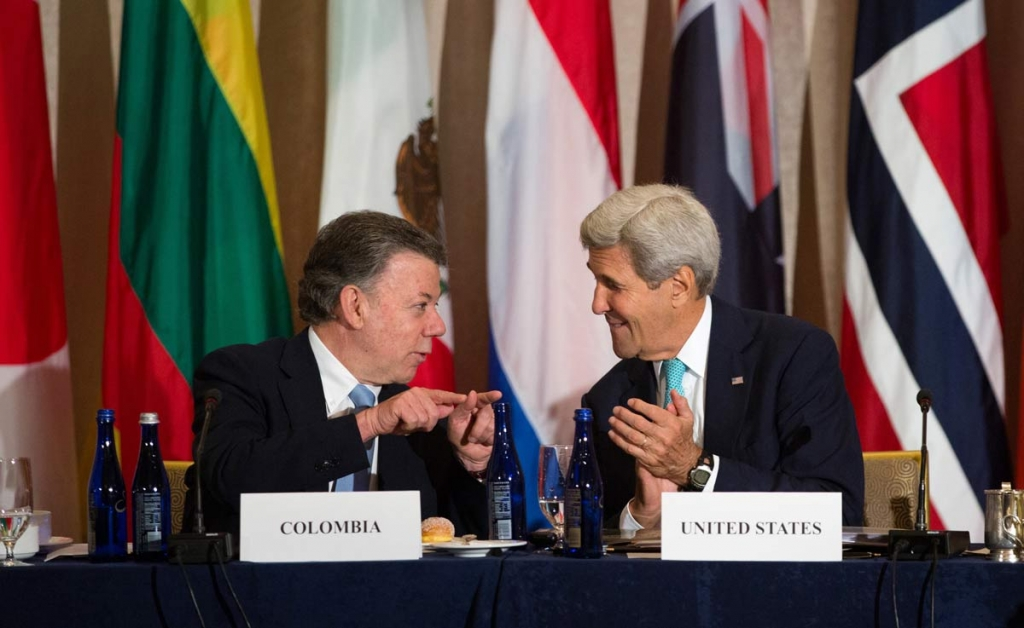 U.S. Secretary of State John Kerry right talks with President Juan Manuel Santos of Colombia during the Global Demining Initiative for Colombia meeting Sunday Sept. 18 2016 in New York