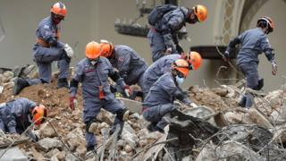 Rescue teams work in the rubble of the building that collapsed as the result of a huge blaze in the centre of Sao Paulo on 8 May 2018