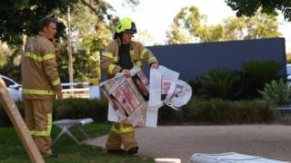 Fire crews remove evidence in bags marked asbestos from South Korea's consulate in Melbourne