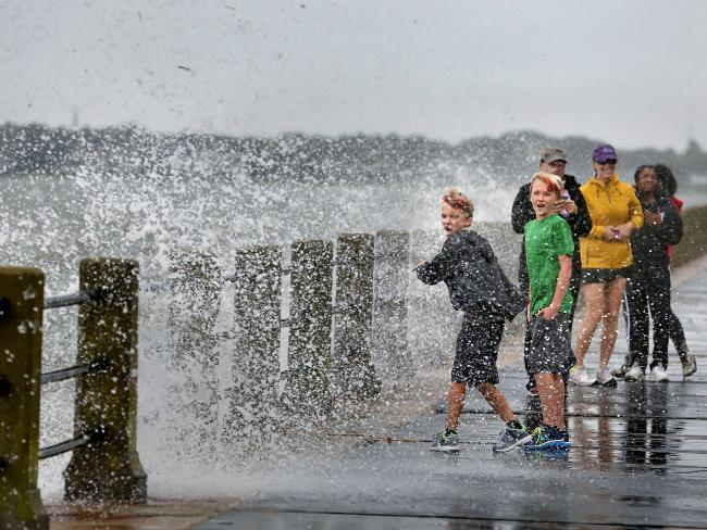 Brothers Trey Bowers, 10 and Tyler Bowers, 12, are splashed with salt water from a crashing wave from Tropical Storm Hermine in Charleston, South Carolina. Picture: AP