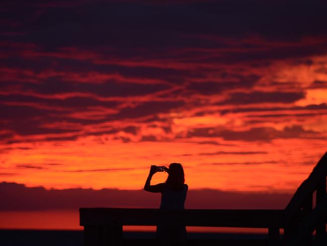 Karen Duer-Potts uses her mobile phone to take a photograph of the sunset as the outer band of Hermine, which has weakened to a tropical storm, creeps over the beach at Cape Charles, Virginia. Picture: AP