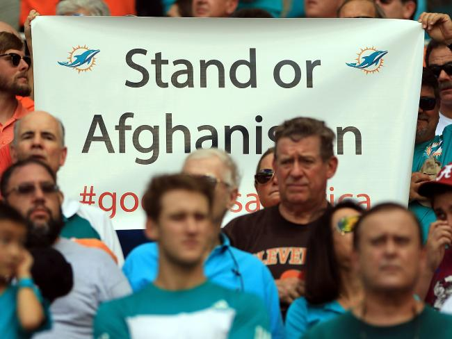 A Miami Dolphins fan holds up a banner protesting the kneeling by players. Picture: Marc Serota/Getty Images/AFP