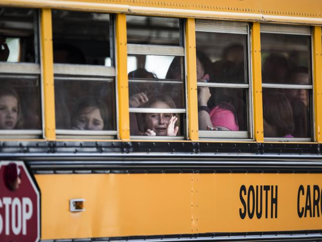 Townville Elementary students look out of the window of a school bus as they are transported to a local church following the shooting. Picture: Katie McLean/The Independent-Mail via AP