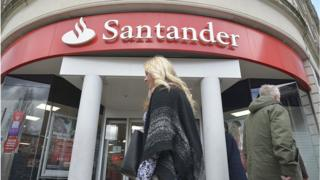 A woman walks past Santander bank in the UK