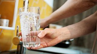 Person filling glass of water.