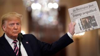 Trump holds newspaper reading, 'acquitted'