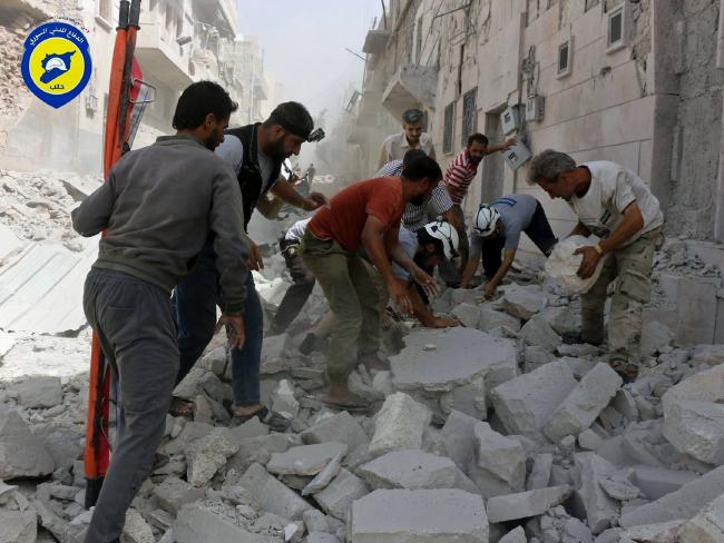 Rescue workers search for survivors under the rubble following air strikes in the al-Sakhour neighbourhood of the rebel-held part of eastern Aleppo, Syria. Picture: Syrian Civil Defence White Helmets via AP