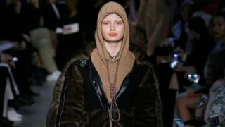A model wears the hoodie featuring a noose around the neck