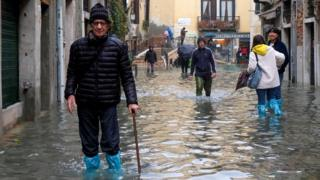 People walk the streets of Venice during exceptionally high water levels, 13 November 2019