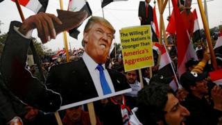 Supporters of Iraqi Shia cleric Moqtada al-Sadr carry placards depicting Donald Trump
