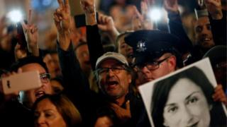People demonstrate calling for the resignation of Joseph Muscat