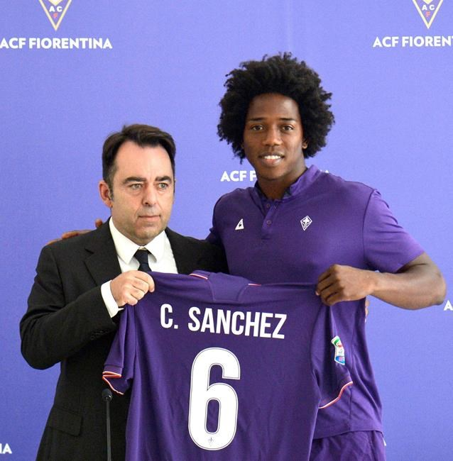 Colombia's Carlos Sanchez right poses with the jersey of his new soccer team Fiorentina during the official presentation in Florence Italy Wednesday Aug. 17 2016
