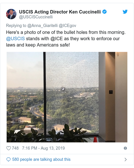 Twitter post by @USCISCuccinelli: Here's a photo of one of the bullet holes from this morning. @USCIS stands with @ICE as they work to enforce our laws and keep Americans safe!