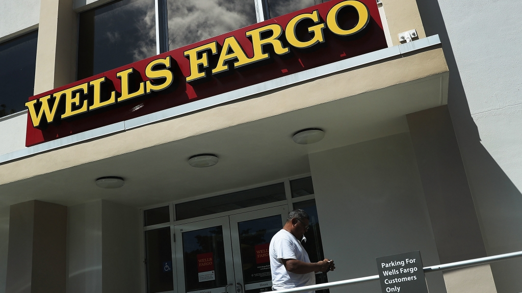 A Wells Fargo executive's departure with large stock and options holdings has sparked questions after the division she ran incurred $185 million in penalties