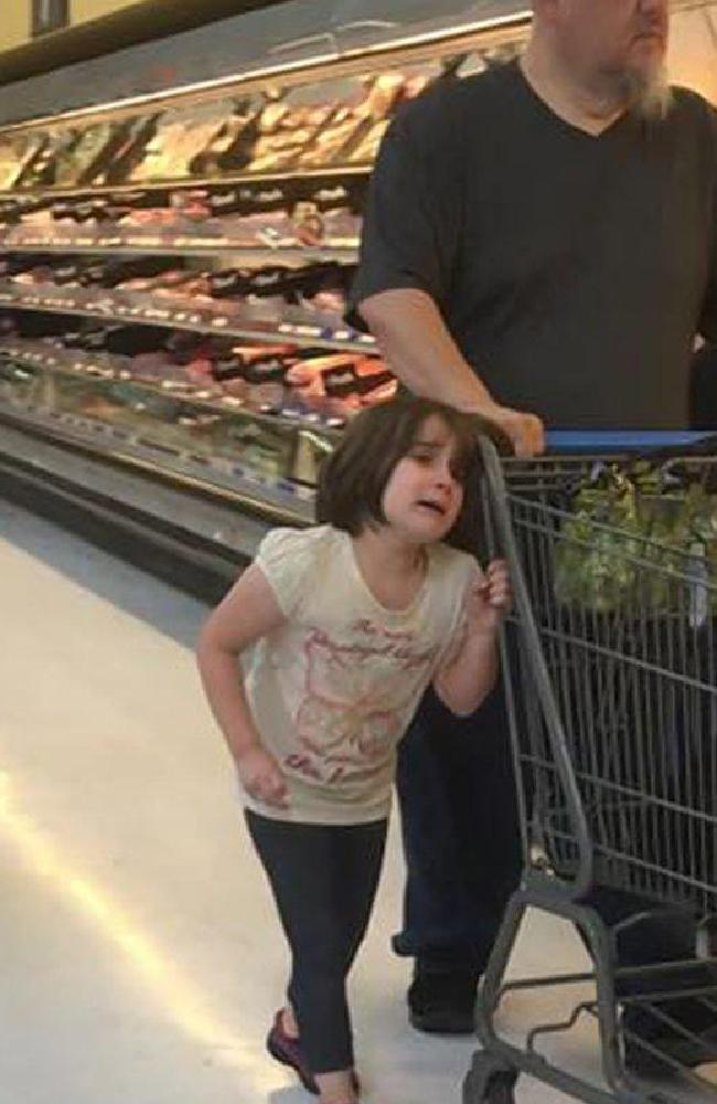 The young girl allegedly yells quot;please stop. I promise I won't do it again. Please stop!quot; as her father pulls the shopping trolley with her hair pulled around the shopping trolley. Picture: Erika Burch / Facebook