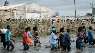 People wade through floodwater in Mozambique