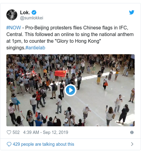 Twitter post by @sumlokkei: #NOW - Pro-Beijing protesters flies Chinese flags in IFC, Central. This followed an online to sing the national anthem at 1pm, to counter the Glory to Hong Kong singings.#antielab