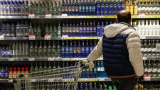 A man looks at a display of bottles of alcohol at a supermarket in Moscow