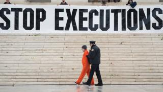 Protesters erecting a large banner reading stop executions outside the US Supreme Court in 2017