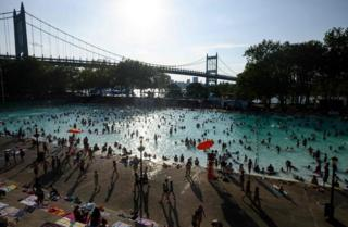 People enjoy the Astoria Pool on a hot afternoon in the borough of Queens, New York City, on July 20, 2019