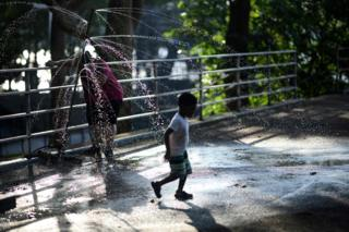 A boy cools down in a spring in the Astoria Park in the borough of Queens on July 20, 2019